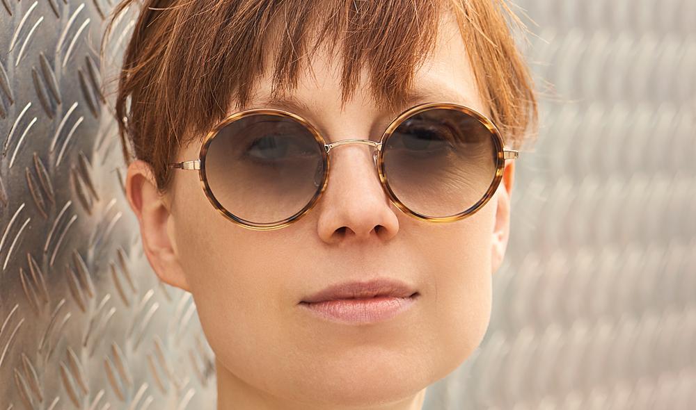 Garrett Leight – Sonnenbrille – Model Kalisa – runde Brille aus goldenem Metall mit braunen Acetatringen mit braun verlaufenden Gläsern - KITSCHENBERG Brillen