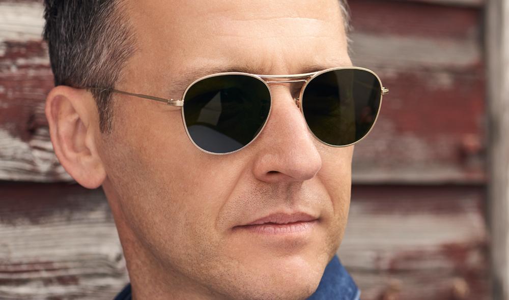 Oliver Peoples – Sonnenbrille - Model Mikael – feine goldene Brille mit leichter Ziselierung am Rand und dunkelgrünen Gläsern - KITSCHENBERG Brillen
