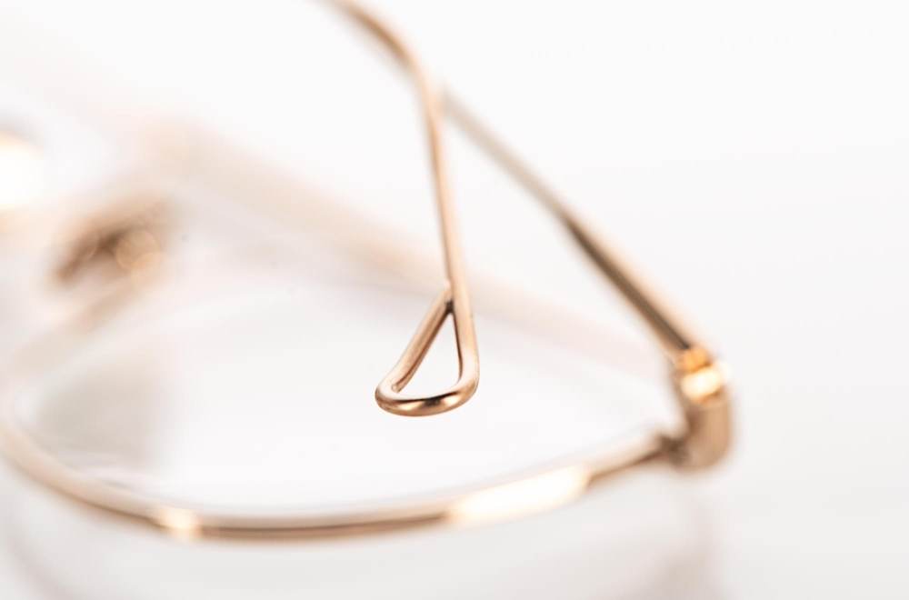 Yellows Plus – Detail eines Bügels einer goldenen Titan Brille - KITSCHENBERG Brillen