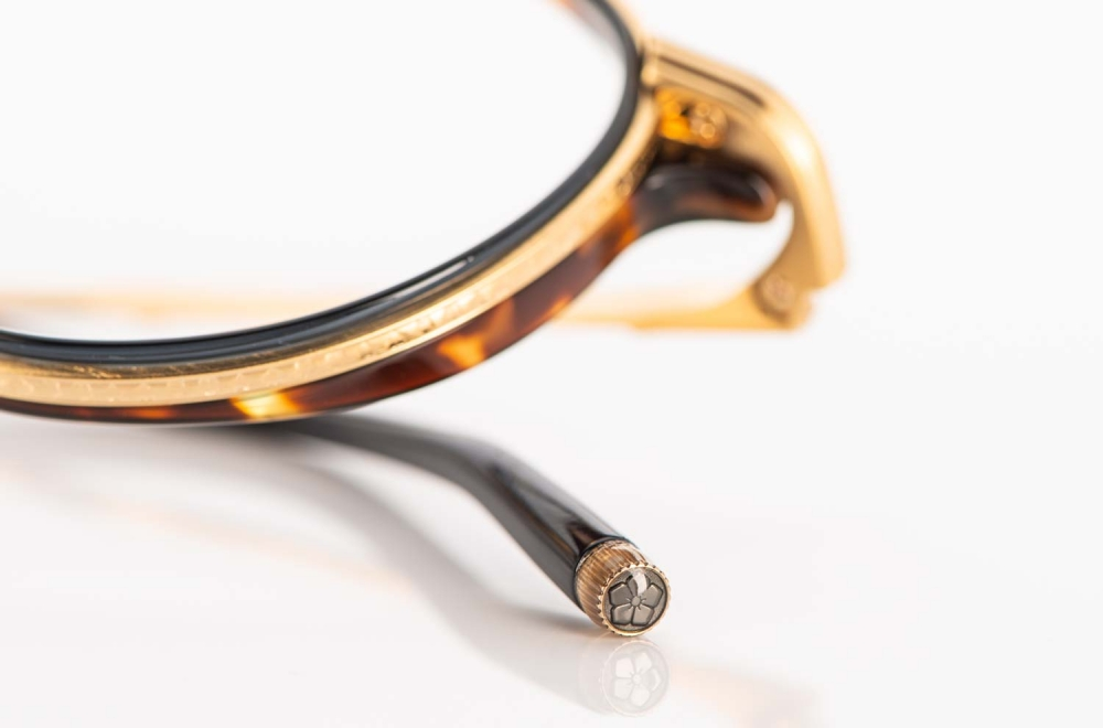 Masunaga – Brillenrand einer ziselierten goldenen Titan Brille mit schwarzer und havanna farbiger Acetat Einlage - KITSCHENBERG Brillen