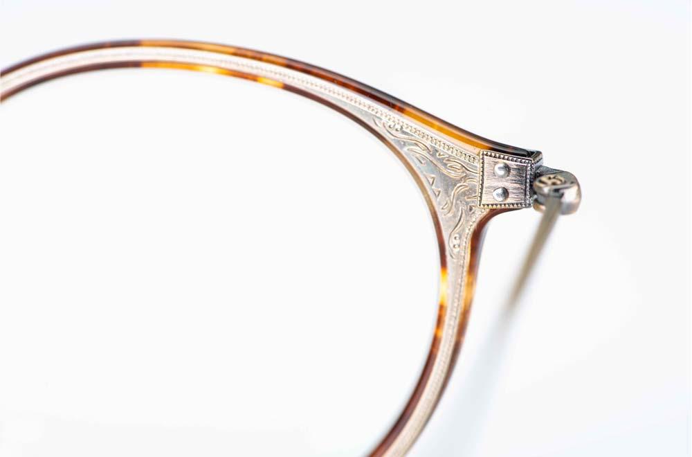 Eyevan – Detail einer ziselierten einlaminierten Metalleinlage in einer runden Acetatbrille - KITSCHENBERG Brillen